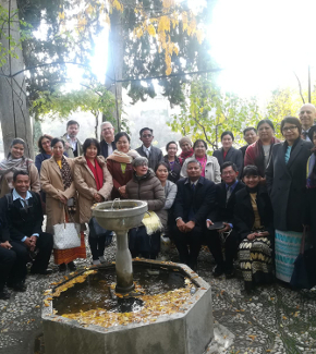 Representatives from the different partner universities posing for a photo outside beside a fountain